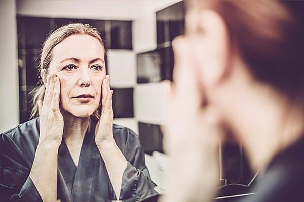 Women Rubbing Her Face In Mirror
