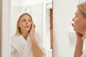 Woman looking at aged skin in mirror