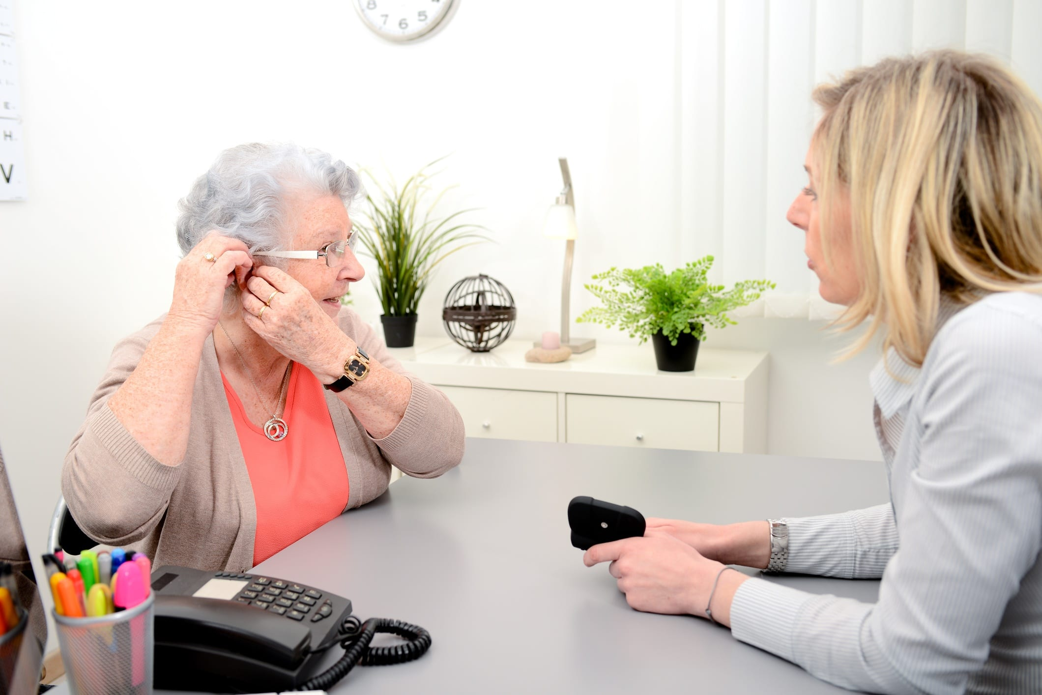 Woman speaking to a hearing aid specialist about her hearing aid