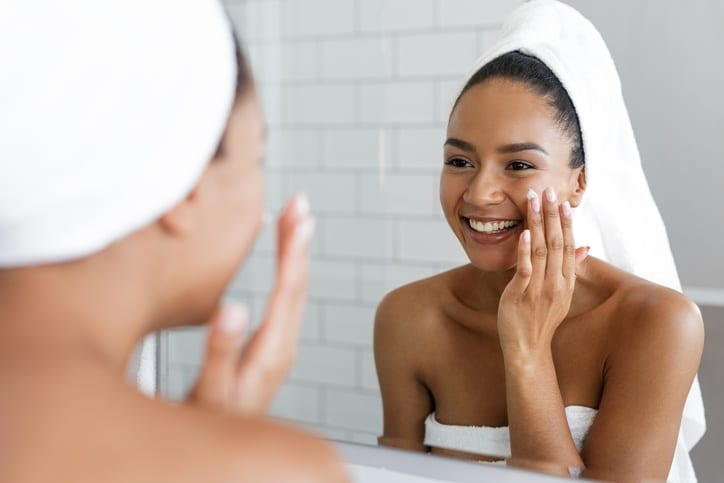 Woman Looking In The Mirror Skincare