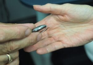 Hearing Aid in Hand- Wearing Hearing Aids